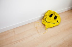 Deflated smiling face balloon on floor