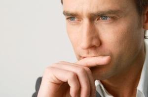 Homem-com-semblante-pensativo-tendo-uma-das-maos-proxima-a-boca